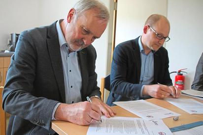 Wilfried Roos als Vorsitzender des Fördervereins Klimakommune Saerbeck und Maarten Willenbrink, kommissarischer Leiter der Maximilian-Kolbe-Gesamtschule, unterzeichnen die sechs Punkte starke Vereinbarung. Foto: Jan-Philipp Jenke
