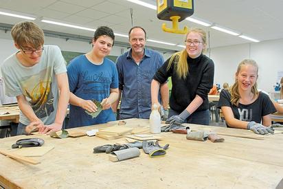 Handarbeit steckt in den Upcycling-Werkstücken, die Innenarchitekt Oliver Schübbe (M.) mit MKG-Schülern aus gebrauchtem Material herstellt. Foto: Alfred Riese