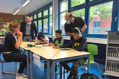 Christiane Althoff (li.), Maarten Willenbrink (hinten) und Niels Effelsberg freuen sich mit den jungen Schülern über die neue Möglichkeit der digitalen Förderung. Die drei Jungs übrigens müssen keine Maske tragen - es sind Brüder. Foto: Martin Weßeling