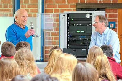 Der Zeitzeuge des Weltkrieg-Endes in Saerbeck, Alfred Maimann (links), mit Josef Berkemeier vom Heimatverein vor Schülern der MKG. Foto: Alfred Riese