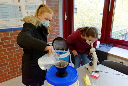 Chemie praktisch: Mit einer Camping-Waschmaschine, einem Filter und dem Mikroskop zeigen Katja (rechts) und Amelie Mikroplastik-Abrieb im Wasser - das gibt es wirklich und es ist ein Problem. Foto: Gemeinde Saerbeck